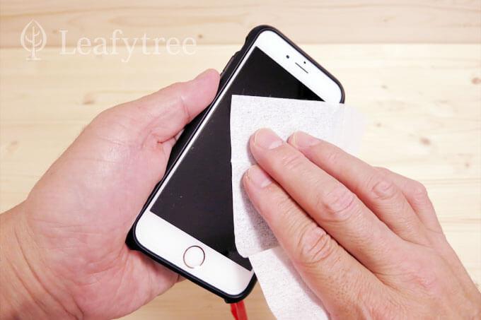 スマートフォンの画面をメガネ拭きのシートで拭きます